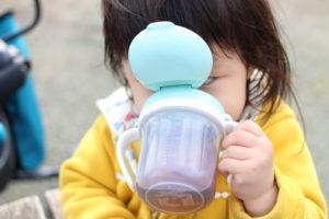 子どもがストローマグでお茶を飲む画像です